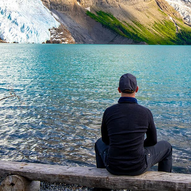 Man contemplating a lake and mountains